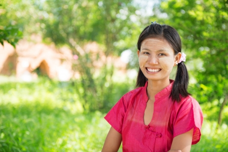 Portrait of happy smiling beautiful young traditional Myanmar girl standing outdoor. Stock Photo - 22112479