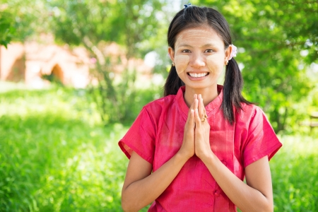burmese: Portrait of happy smiling beautiful young traditional Myanmar girl in welcoming pose at outdoor. Stock Photo