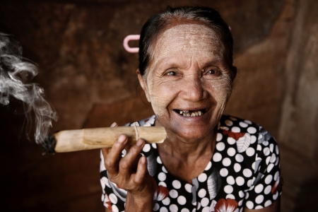 old: Happy old wrinkled Asian woman smoking traditional tobacco. Bagan, Myanmar.