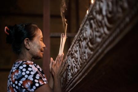 incienso: Vieja arrugada mujer tradicional asiática que ruega con los palillos de incienso en el interior de un templo, con poca luz, Myanmar Foto de archivo