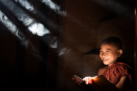 Southeast Asian little monk reading book inside monastery, beautiful natural light shining thru. Stock Photo