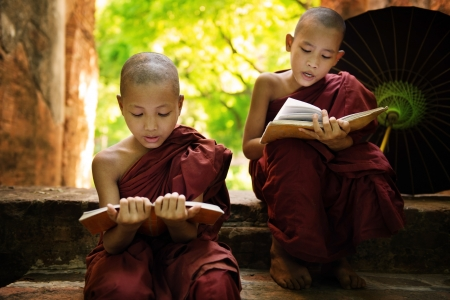 smiling buddha: Southeast Asian Myanmar little monk reading book outside monastery, Buddhist teaching. Stock Photo
