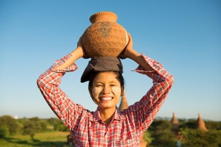 伝統: 家に帰るつもり、バガン、ミャンマーの頭の上の粘土の鍋を運ぶアジアの伝統的な女性の農民の肖像画