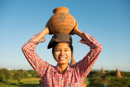 Portrait of Asian traditional female farmer carrying clay pot on head going back home, Bagan, Myanmar photo