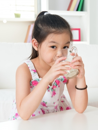 Drinking milk. Happy Asian kid drink milk at home. Beautiful child. Healthcare concept. photo