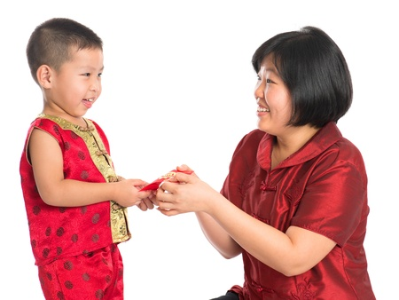 ang: Asian Chinese boy receiving red paper packet or monetary from parent on Chinese New Year festival, with traditional Cheongsam isolated on white background.