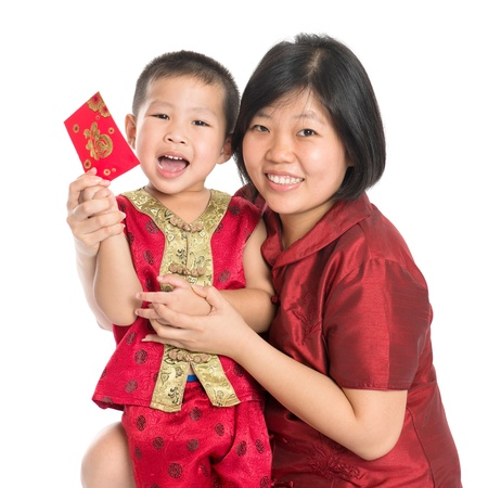 Asian Chinese child receiving monetary gift or red paper packet from parent on Chinese New Year festival, with traditional Cheongsam isolated on white background. photo