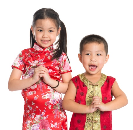 Little oriental girl and boy wishing you a happy Chinese New Year, with traditional Cheongsam standing isolated on white background.