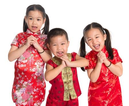 Kleine oosterse kinderen die u een gelukkig Chinees Nieuwjaar wensen, met traditionele Cheongsam-status geïsoleerd op witte achtergrond.