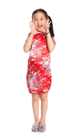 Full length China girl in traditional Chinese cheongsam dress shouting Happy Chinese New Year to everyone,  standing isolated on white background photo