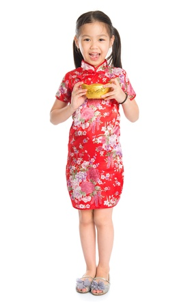Full length China girl in traditional Chinese cheongsam dress greeting, holding a gold ingot standing isolated on white background