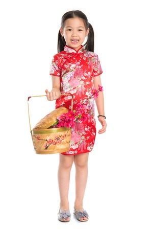 hand basket: Full length China girl in traditional Chinese cheongsam dress holding a gift basket standing isolated on white background