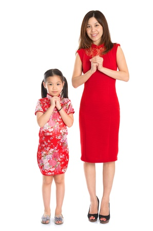Happy Chinese New Year! Full body Chinese parent and child in traditional Chinese cheongsam greeting to each other, isolated on white background photo
