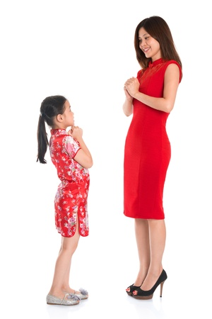 each year: Happy Chinese New Year! Full length Chinese parent and child in traditional Chinese cheongsam greeting to each other, isolated on white background Stock Photo