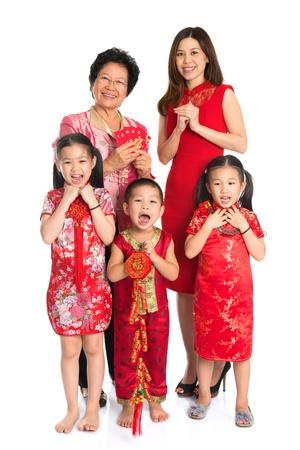 Groupe des heureux à plusieurs générations d'Asie famille chinoise vous souhaitant un joyeux nouvel an chinois, avec Cheongsam traditionnel debout isolé sur fond blanc.