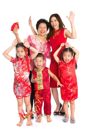 Group of happy  smiling multi generations Asian Chinese family wishing you a happy Chinese New Year, with traditional Cheongsam standing isolated on white background. photo