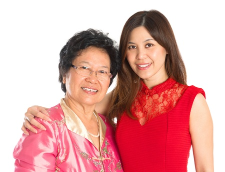 two year old: Chinese New Year festival. Happy Asian Chinese senior mother and adult daughter standing isolated on white background