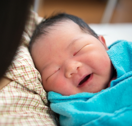 asian hospital: Newborn Asian baby girl smiling and fall asleep in mothers arms, inside hospital room