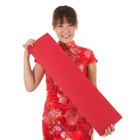 Asian woman with Chinese traditional dress cheongsam or qipao holding couplet, Isolated on white background. photo