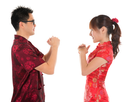 Side view Asian man and woman with Chinese traditional dress cheongsam. Chinese new year concept, isolated on white background. Stock Photo - 22284186