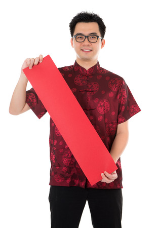 Asian man with Chinese traditional cheongsam or tang suit holding couplet. Male model isolated on white background. photo