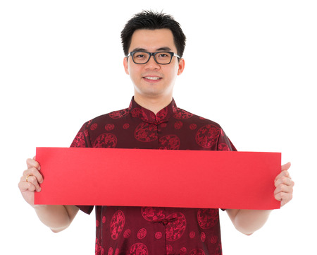 Asian male with Chinese traditional cheongsam or tang suit holding couplet. Male model isolated on white background. photo