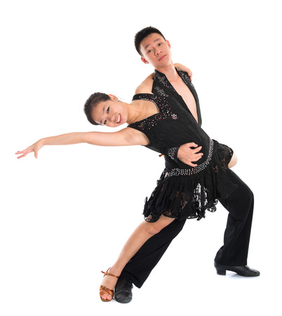 Young Asian teens couple latin dancers dancing in front of the studio background, full length isolated white.
