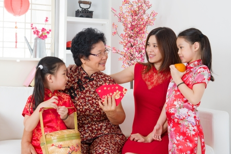 traditional celebrations: Happy multi generations Asian family celebrate Chinese new year at home. Stock Photo