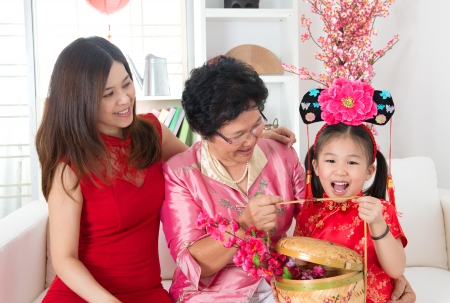 grandparent: Beautiful grandchild visiting grandparent with gift during Chinese new year festival.
