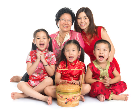 new: Group of happy multi generations Asian Chinese family wishing you a happy Chinese New Year, with traditional Cheongsam sitting isolated on white background.