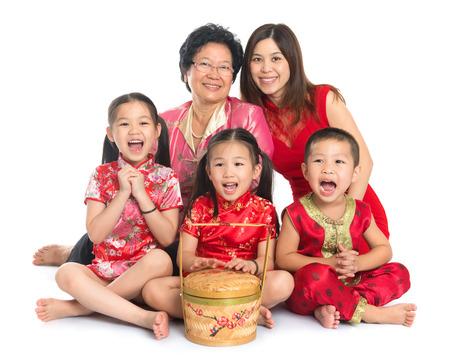 generace: Skupina happy multi generací asijské čínská rodina vás, kteří si přejí šťastný čínský Nový rok, s tradiční Cheongsam sedí na bílém pozadí.