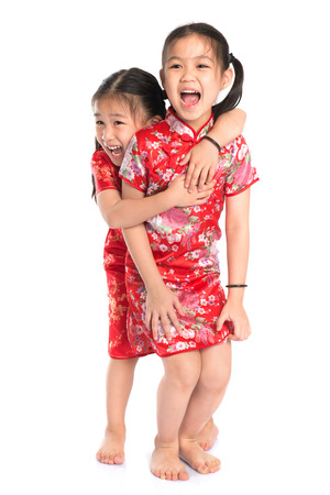 Beautiful oriental Asian girls in traditional Chinese cheongsam playing, full length isolated on white background photo