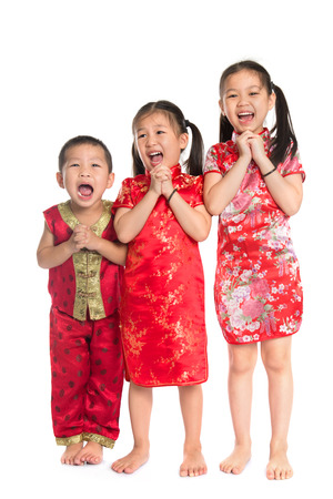 cheongsam: Little oriental children wishing you a happy Chinese New Year, with traditional Cheongsam standing isolated on white background. Stock Photo