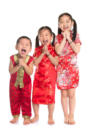 Group of oriental children wishing you a happy Chinese New Year, with traditional Cheongsam full length standing isolated on white background. photo