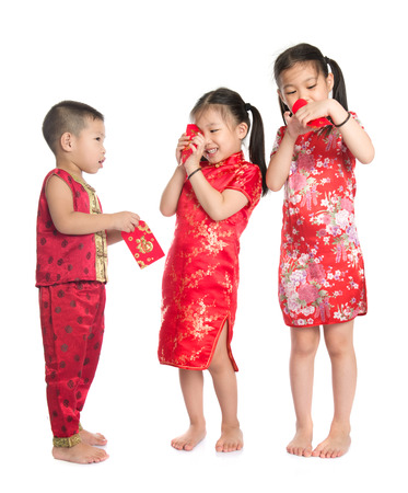 chinese culture: Asian children peeking into red packet during Chinese New Year, with traditional Cheongsam full length standing isolated on white background. Stock Photo