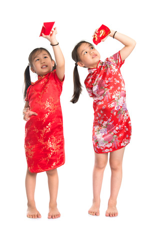Happy Asian girls peeking into red packet during Chinese New Year, with traditional Cheongsam full length standing isolated on white background. photo