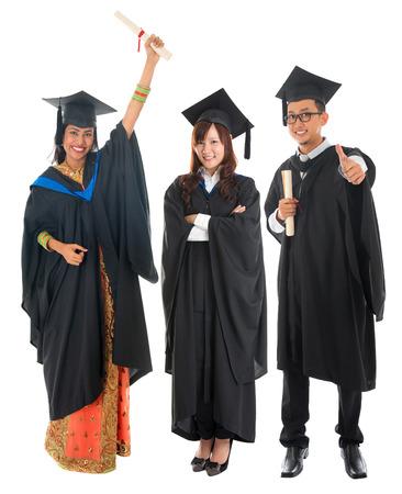 Grupo de todo el cuerpo de múltiples razas estudiante universitario en traje de graduación de pie aislado en fondo blanco