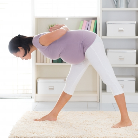 Prenatal yoga. Full length healthy 8 months pregnant calm Asian woman meditating or doing yoga exercise at home. Relaxation yoga forward bending pose. photo