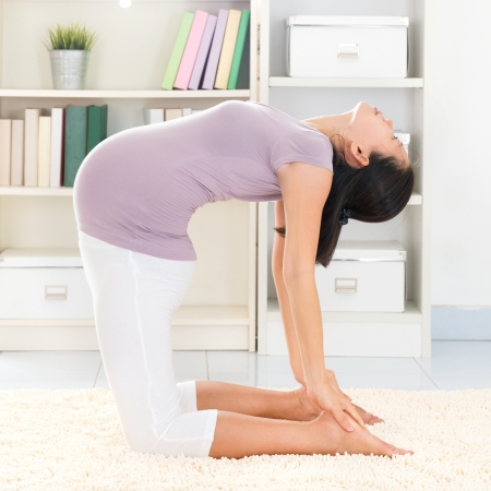 Maternity health concept. Full length healthy 8 months pregnant calm Asian woman meditating or doing yoga exercise at home. Relaxation. Yoga camel pose. photo