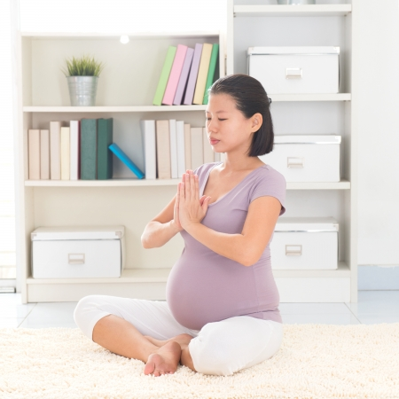 pregnancy yoga: Pregnancy yoga meditation. Full length healthy 8 months pregnant calm Asian woman meditating or doing yoga exercise at home. Relaxation yoga positions.