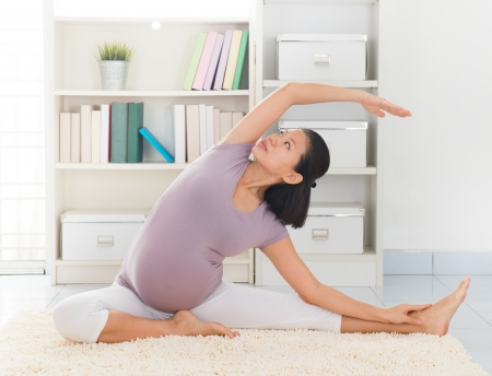 8 months pregnancy: Pregnancy yoga meditation. Full length healthy 8 months pregnant calm Asian woman meditating or doing yoga exercise at home. Relaxation yoga sitting side stretch positions.