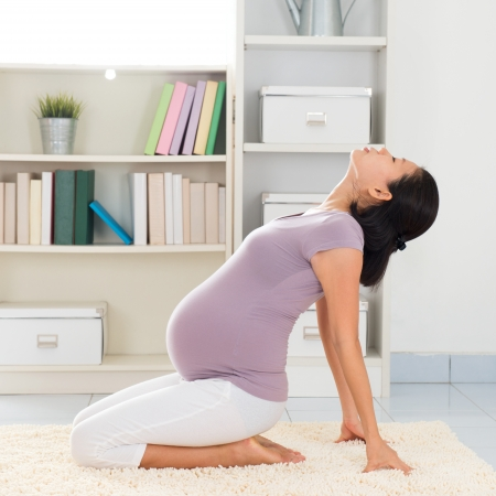 8 months pregnancy: Pregnancy yoga meditation. Full length healthy 8 months pregnant calm Asian woman meditating or doing yoga exercise at home. Relaxation yoga sitting back bending positions.