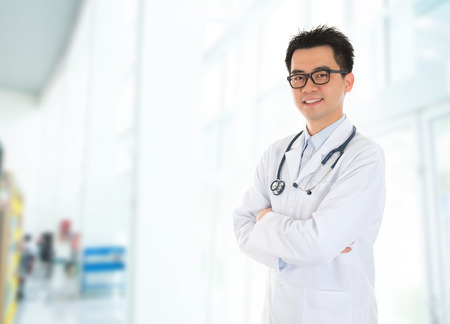 Asian male medical doctor with confident smile standing inside hospital building.