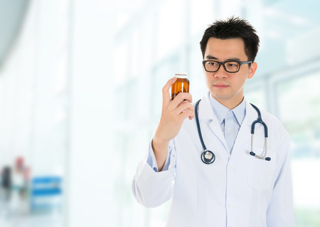 Asian male medical doctor holding a bottle of drugs, standing inside hospital building. photo
