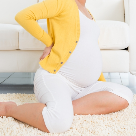 aches: Back pain. 8 months pregnant woman holding her back while sitting on a floor at home.