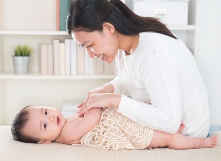 asian baby: Asian mother giving massage to baby girl at home. Stock Photo