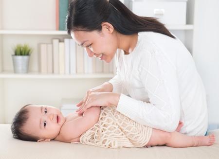 madre y bebe: Madre que da masajes a la ni�a en casa. Foto de archivo