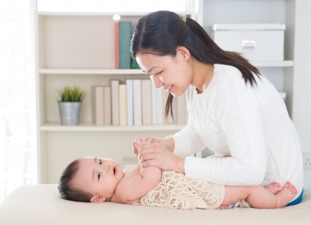 Baby massage. Asian mother massaging baby hands at home. photo