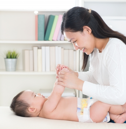 asian baby: Asian mother playing with baby girl at home. Stock Photo