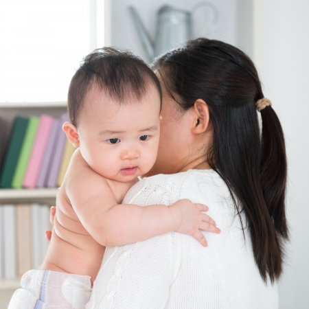 caretaking: Asian mother pampering six months old baby girl at home.